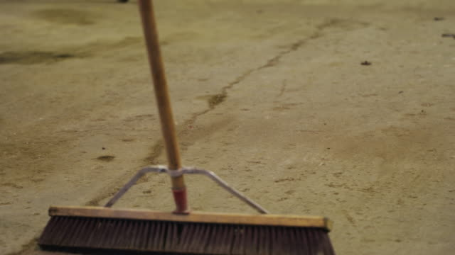Close up man with large broom sweeps the concrete floor of a machine shop.