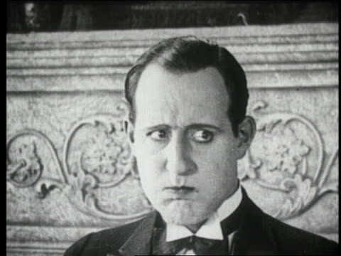 b/w 1924 close up man with mouth full looking from left to right suspiciously - suspicion stock videos & royalty-free footage