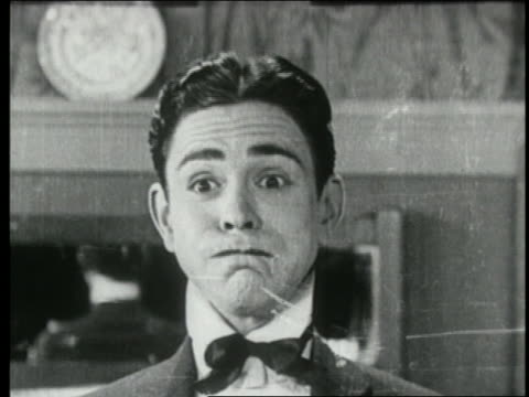 stockvideo's en b-roll-footage met b/w 1924 close up man with mouth full smiling, then frowns + looks off screen - angst