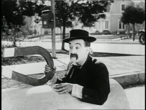 b/w 1923 close up man with mustache (snub pollard) sitting in mini-car with giant magnet / feature - 1923 stock videos & royalty-free footage