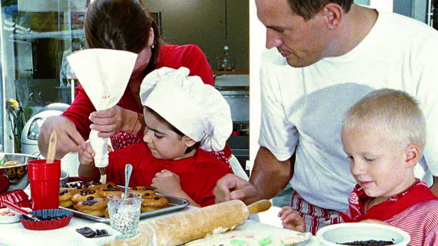 close up man + woman helping boy + girl prepare food in kitchen - icing stock videos and b-roll footage