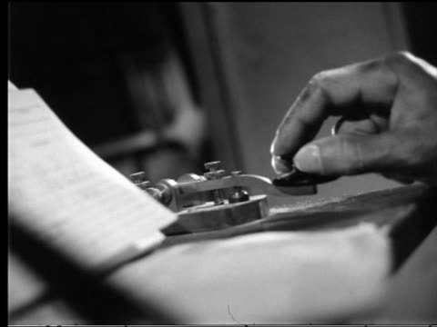 b/w canted close up man's greasy hand typing out message on telegraph key - telegraph machine stock videos & royalty-free footage