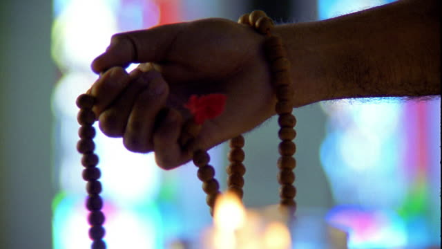 stockvideo's en b-roll-footage met close up man's hand feeling rosary beads - katholicisme