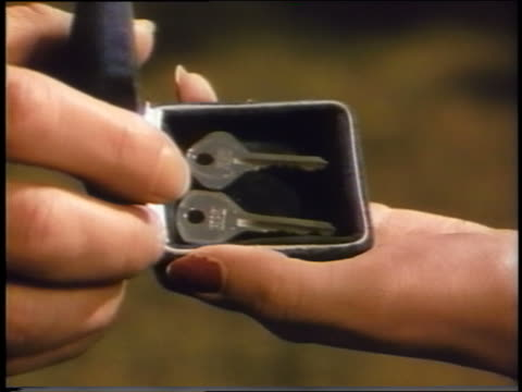 vídeos de stock, filmes e b-roll de 1939 close up man's hand gives two keys in box to woman's hand - chave