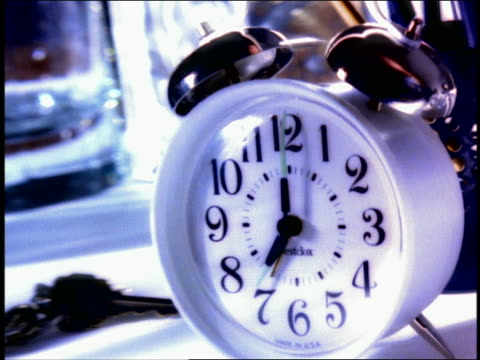 close up man's hand knocking over alarm clock