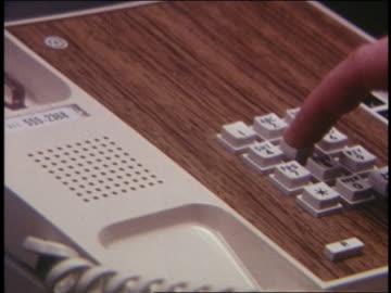 vídeos y material grabado en eventos de stock de 1970 close up pan man's hand picking up telephone receiver - teléfono con cable