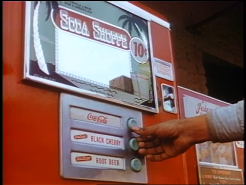 1958 close up man's hand pushing button on soda vending machine / newsreel