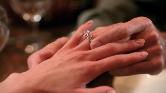 Close up man's hand putting diamond ring on woman's finger