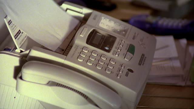 close up man's hand putting paper in fax machine + pushing buttons