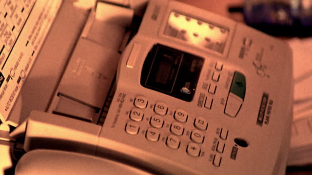 sepia close up man's hand putting paper in fax machine + pushing buttons - fax machine stock videos & royalty-free footage