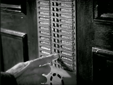 b/w 1949? close up man's hand ringing buzzer on apartment lobby directory - 1949 stock videos & royalty-free footage