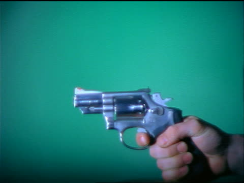 HIGH SPEED close up man's hand shooting revolver with blue background