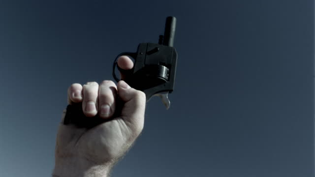 close up man's hand shooting starting gun being shot - sparare video stock e b–roll