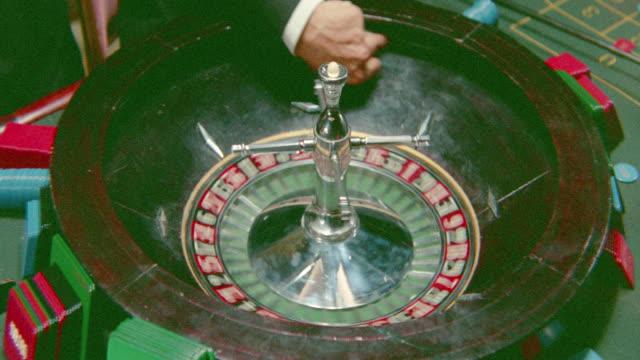 vídeos de stock, filmes e b-roll de close up man's hand spins ball + roulette wheel / three bites of the apple (1966) - jogo da sorte