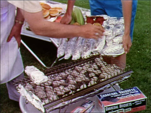 1955 close up man's hand takes aluminum foil wrapped food from tray + puts it on grill outdoor