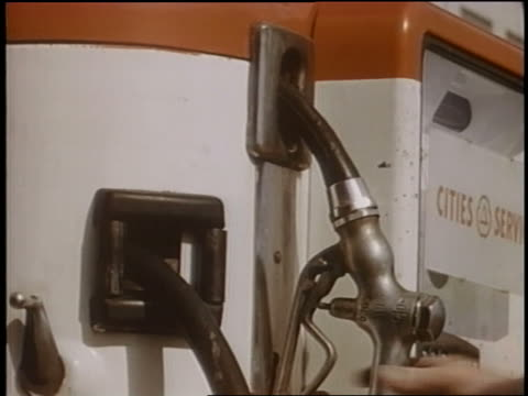 1958 close up man's hand takes nozzle from gas pump - filling station attendant stock videos and b-roll footage