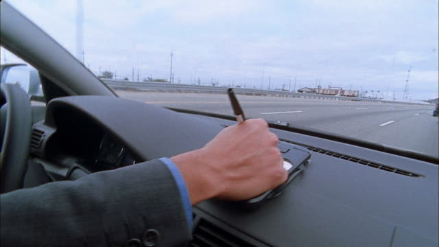 close up man's hand writing note on pad attached to dashboard in moving car - note pad stock-videos und b-roll-filmmaterial