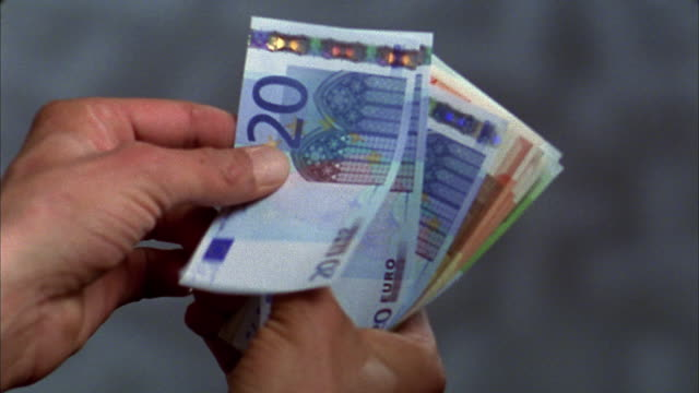stockvideo's en b-roll-footage met close up man's hands counting stack of euro notes - europese unie