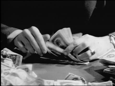 B/W close up man's hands counting stacks of dollar bills on table