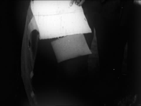 B/W 1922 close up man's hands holding bullet-proof vest / newsreel