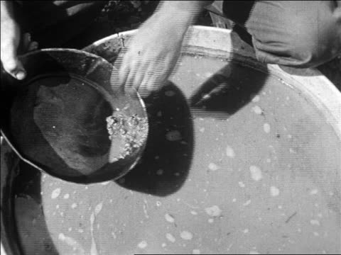 b/w 1927 close up man's hands holding pan with gold over bucket of water / nevada / newsreel - panning stock videos & royalty-free footage