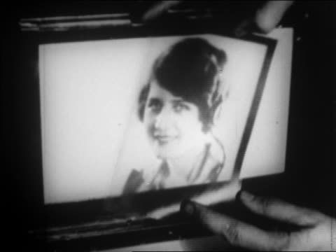 vidéos et rushes de b/w 1924 close up man's hands holding transparency of woman / photo sent by wire / newsreel - 1924