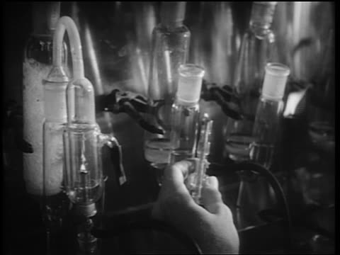 b/w 1952 close up man's hands lighting bunsen burner + attaching it to glass tubes in laboratory - 1952 stock videos & royalty-free footage
