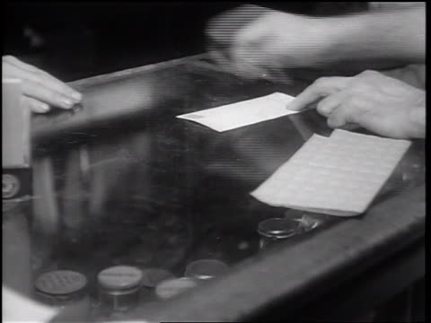b/w 1932 close up man's hands picking up paper slip with stamp from glass countertop / merced - great depression stock videos & royalty-free footage