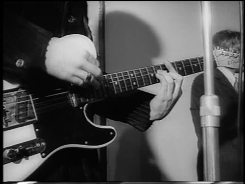 B/W 1966 close up man's hands playing electric guitar / London / newsreel