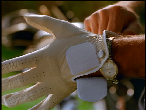 close up man's hands putting golf glove on one hand - golf glove stock videos and b-roll footage