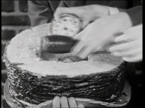 vidéos et rushes de b/w 1933 close up man's hands putting time bomb into cake / in the dough - bombe