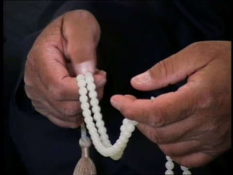 2003 close up man's hands stroking white prayer beads w/praying in background / iraq mosque / audio - prayer beads stock videos & royalty-free footage