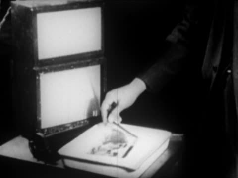 vidéos et rushes de close up man's hands taking photograph from developing tray / photo sent by wire / newsreel - 1924