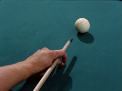 1963 close up man's hands using cue stick to shoot cue ball on pool table / industrial - ビリヤード点の映像素材/bロール