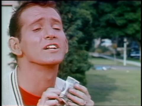 1963 close up man/teen folding up 20 dollar bill while talking proudly outdoors / educational - männlicher teenager allein stock-videos und b-roll-filmmaterial