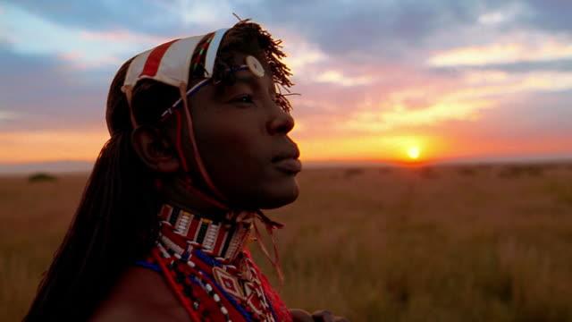 close up masai tribesman looking around + then at camera with sunset in background / kenya - profil sedd från sidan bildbanksvideor och videomaterial från bakom kulisserna