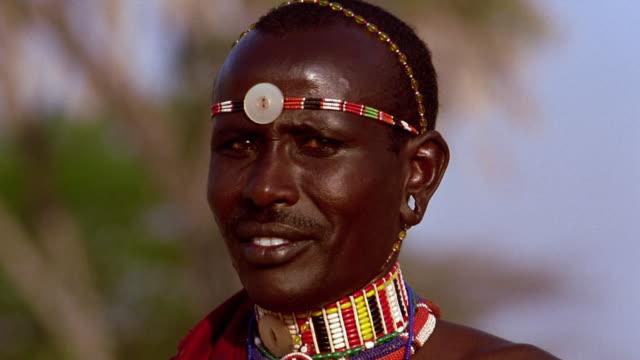 close up masai tribesman turning + looking at camera while smiling / kenya - 民族衣装点の映像素材/bロール