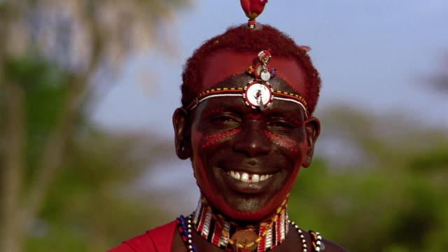 close up Masai tribesman turning + looking at camera while smiling with face paint / Kenya