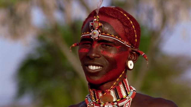 close up masai tribesman turning + looking at camera while smiling with face paint / kenya - whatif点の映像素材/bロール