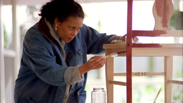 Close up mature Black woman carefully examining and applying varnish to wooden chair w/brush