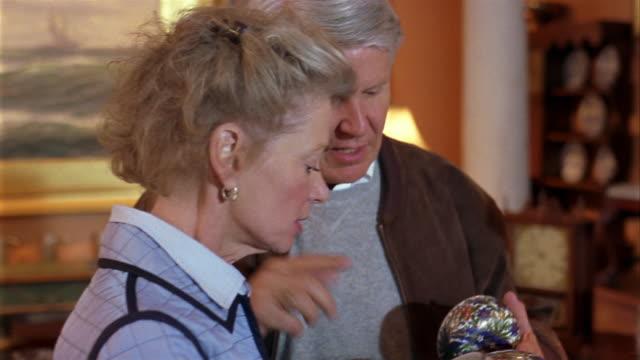 vídeos de stock, filmes e b-roll de close up mature couple looking at vase in antique store - antiquário loja