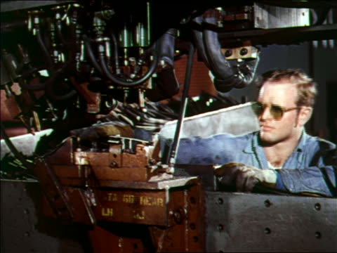 1951 close up men in safety glasses working on car doors on assembly line / Chevrolet factory
