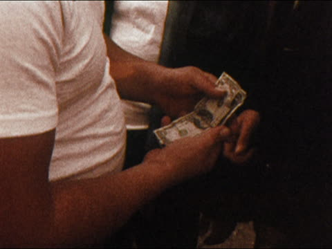 1971 close up men's hands exchanging money in a drug deal