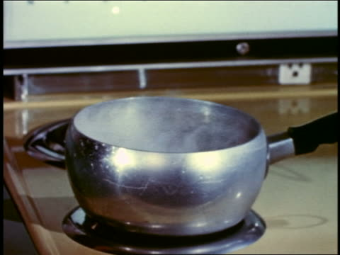 1958 close up metallic saucepan with boiling water being removed from stovetop electric burner - cooking pan stock videos & royalty-free footage