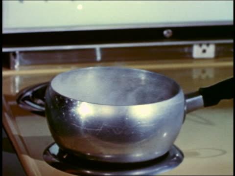 vídeos y material grabado en eventos de stock de 1958 close up metallic saucepan with boiling water being removed from stovetop electric burner - ollas y cacerolas