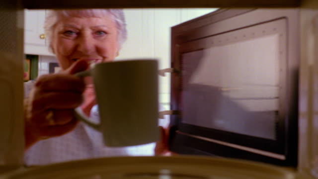 close up microwave point of view senior woman putting coffee cup in microwave, heating + removing - microwave stock videos & royalty-free footage
