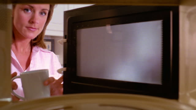 close up microwave point of view woman putting coffee cup in microwave, heating + removing - microwave stock videos & royalty-free footage