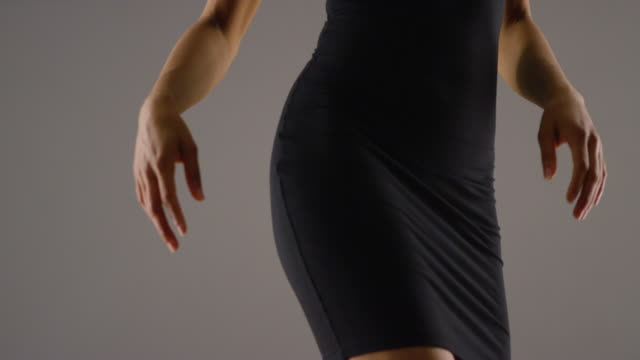 Close up mid section of woman in dress dancing in slowmo