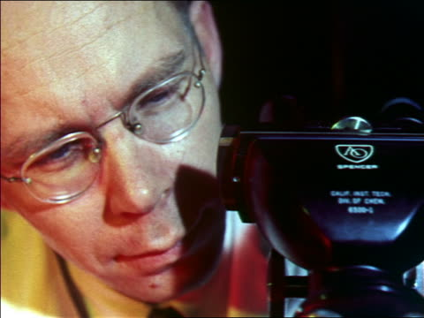 1956 close up middle age male scientist in eyeglasses looking through electron microscope