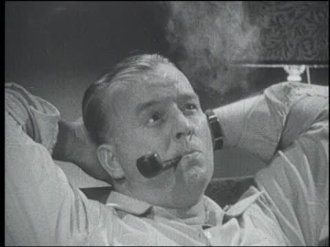 b/w 1951 close up middle aged man smoking pipe while resting head on hands - 1951 bildbanksvideor och videomaterial från bakom kulisserna